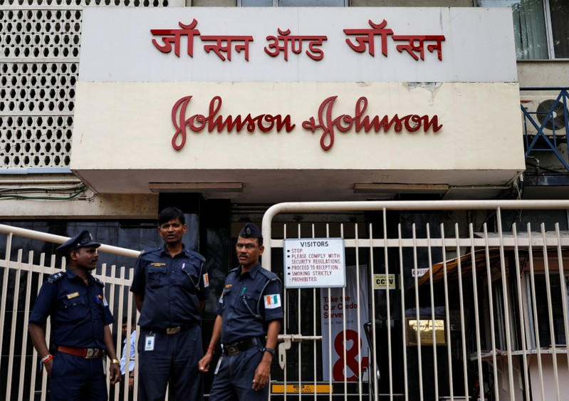 Security guards stand outside the office of Johnson & Johnson in Mumbai