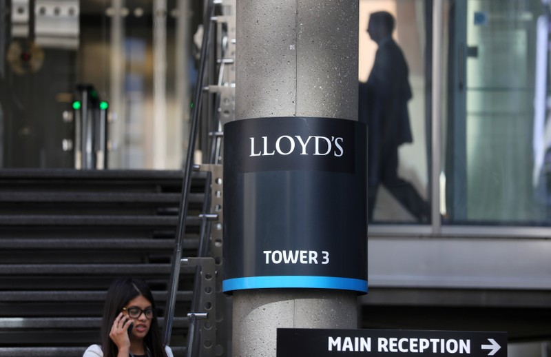 A woman speaks on her mobile phone as she walks out of Lloyds of London's headquarters in the City of London