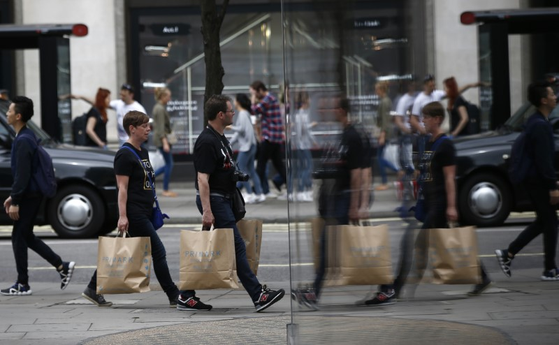Shoppers are reflected in a window as they walk along Oxford Street in London