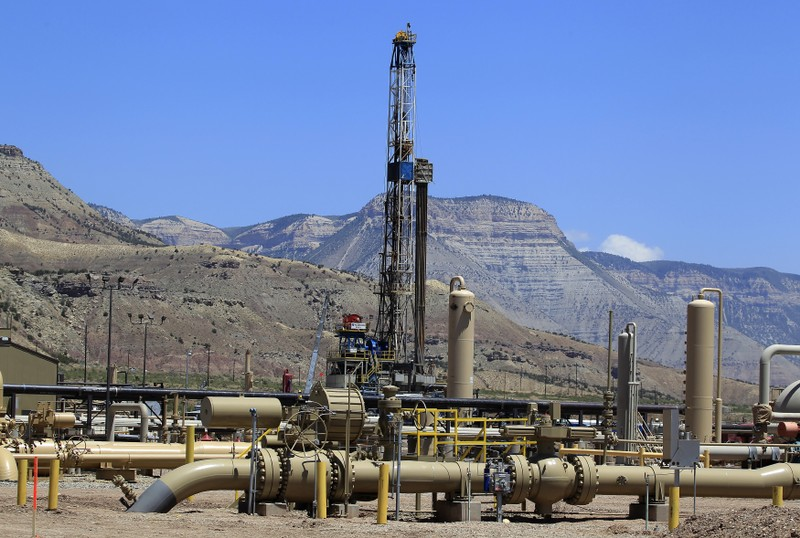 A natural gas drilling rig operates as natural gas piping rises from underground outside  Rifle