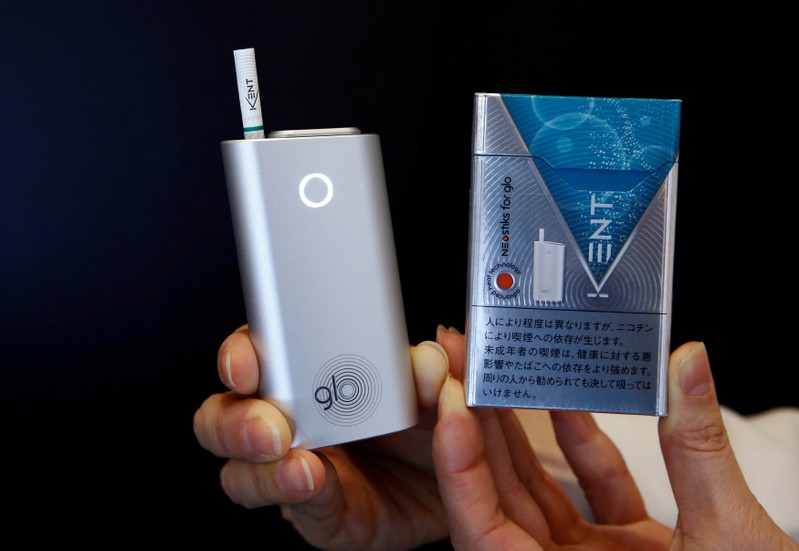 FILE PHOTO: A promoter shows British American Tobacco's new tobacco heating system device 'glo' (L) and Kent tobacco after a news conference in Tokyo, Japan