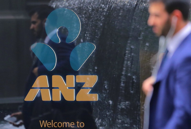 FILE PHOTO: A pedestrian is reflected in the window of a branch of the Australia and New Zealand Banking Group (ANZ) in central Sydney