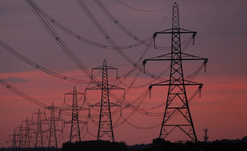 The sun rises behind electricity pylons near Chester