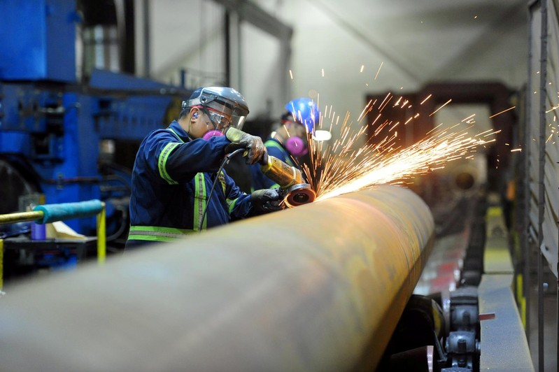 FILE PHOTO: Workers are seen at Bri-Steel Manufacturing, a manufacturer and distributer of large diameter seamless steel pipes, in Edmonton