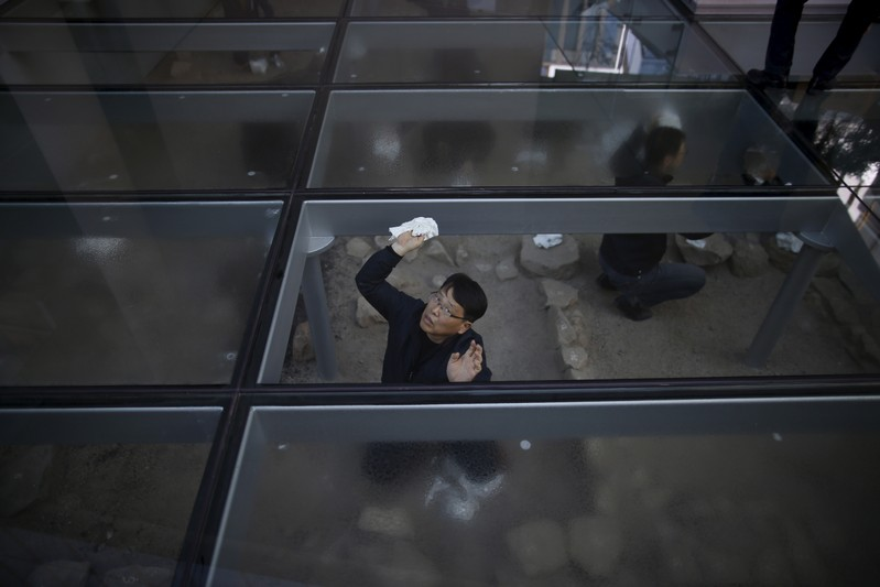 FILE PHOTO:  A worker removes moisture under a glass deck in front of an office building in Seoul