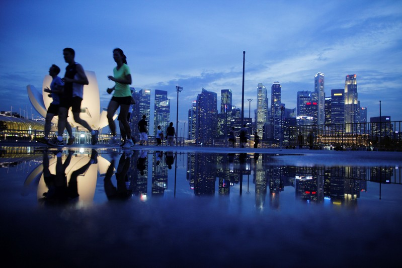 FILE PHOTO:  Joggers run past as the skyline of Singapore's financial district is seen in the background