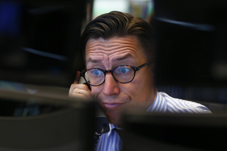 A trader speaks on the phone at his desk at the Frankfurt stock exchange