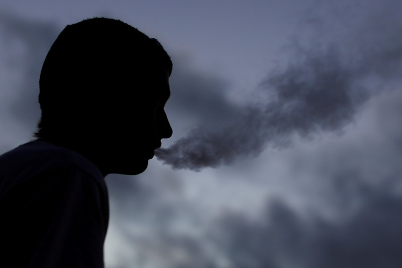 FILE PHOTO: A young man smokes a Suorin Drop electronic cigarette in this picture illustration