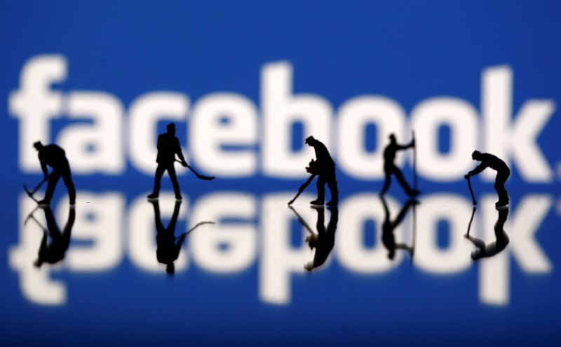 Figurines are seen in front of the Facebook logo in this illustration