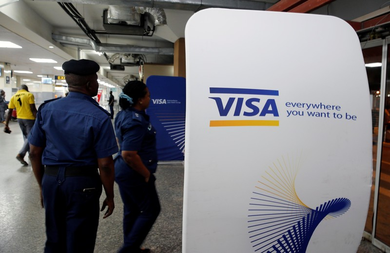 FILE PHOTO:  Security staff stand next to a Visa logo at Murtala Muhammed International Airport before the arrival of the Nigerian Women's Bobsled Team, in Lagos
