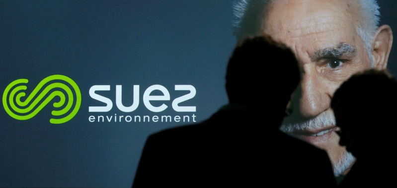 FILE PHOTO: People are silhouetted in front of the new logo of French waste and water company Suez Environnement during a presentation in Paris