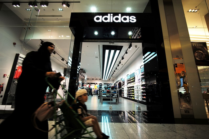 A local woman is seen pushing her baby in front of the Adidas store at Bahrain City Center in Manama