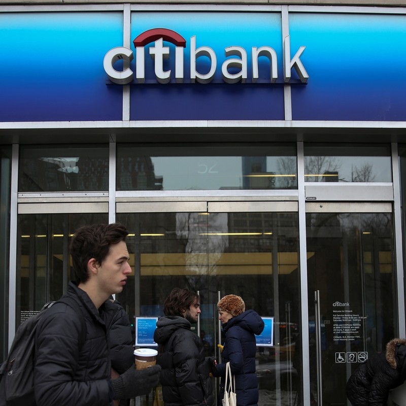 Commuters walk past a Citibank branch in the Manhattan borough of New York