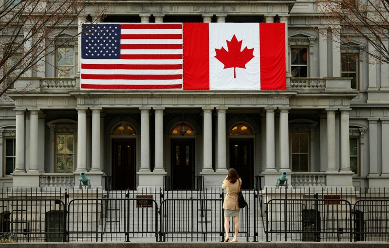 FILE PHOTO: A woman stops to take a photo of the U.S. and Canadian flags placed side-by-side on the Eisenhower Executive Office Building next to the White House in Washington