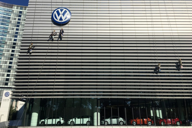 Workers clean the facade of a car showroom under a Volkswagen logo in Beijing