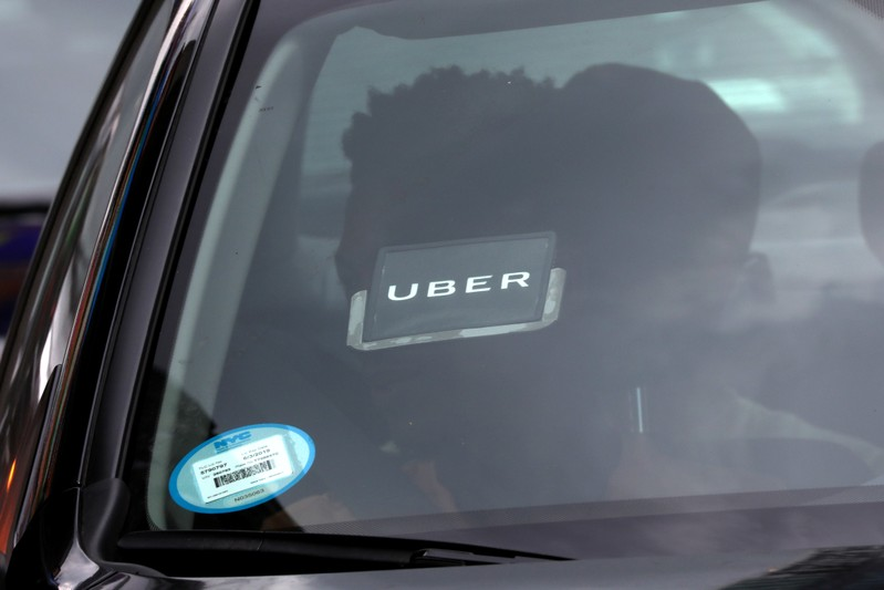 An Uber logo is seen on a car a as it car drives through Times Square in New York City