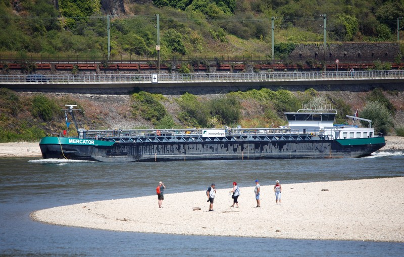 People stroll on a sandbank that is usually covered by the river Rhine in Oberwesel