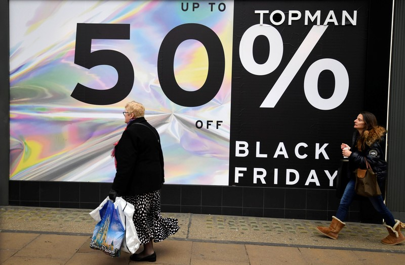 Pers Walk Past Black Friday Signage On Oxford Street In London