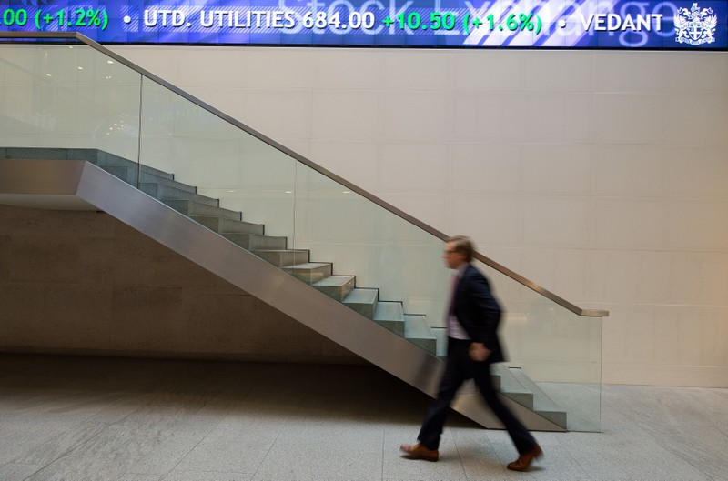 FILE PHOTO:  A man walks under an electronic information board at the London Stock Exchange in the City of London