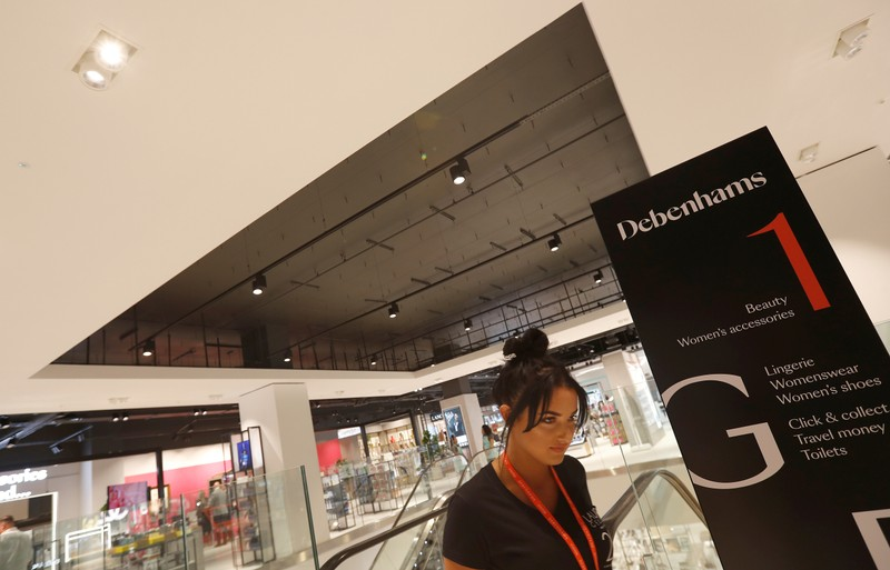 FILE PHOTO: Worker walks on the shop floor of a new Debenhams department store in Watford