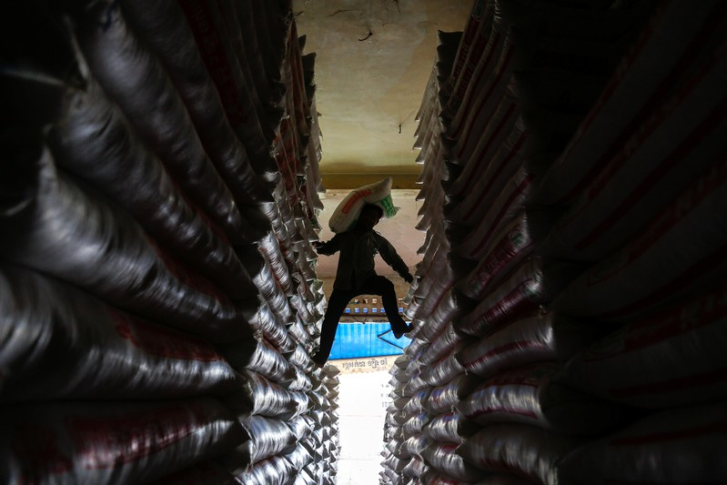 A worker carries a sack of rice at a shop in Phnom Penh