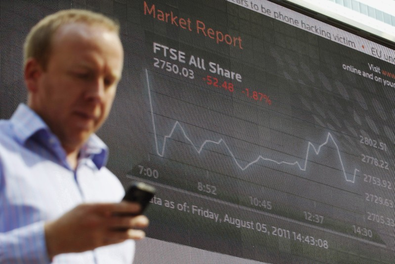 FILE PHOTO:  A man passes a screen showing the activity of the FTSE index at Canary Wharf financial district in London