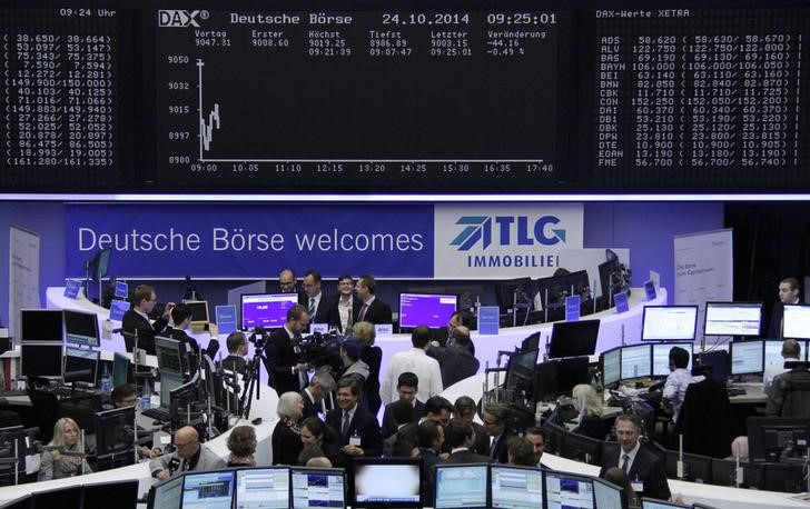 Visitors, attending the Frankfurt stock exchange for the first day of trading in German property group TLG Immobilien, stand in front of the DAX board