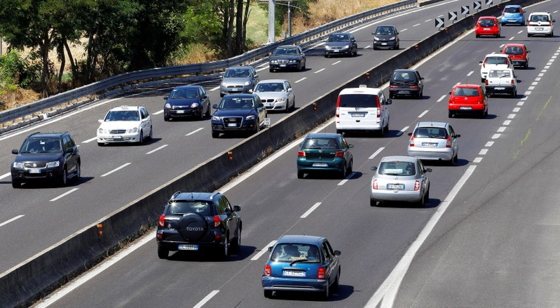 FILE PHOTO: Traffic moves along a road during a hot summer day near Rome