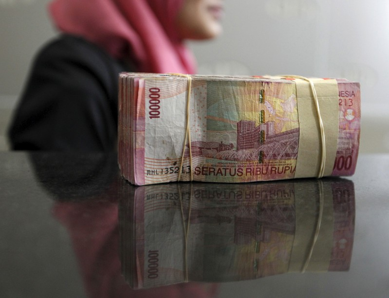 An employee of money changer stands beside Indonesian rupiah banknotes in Jakarta
