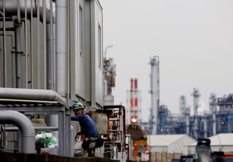 FILE PHOTO : A worker is seen in front of facilities and chimneys of factories at the Keihin Industrial Zone in Kawasaki