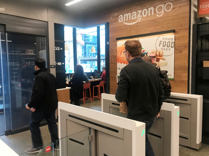 FILE PHOTO: A customer walks out of the Amazon Go store, without needing to pay at a cash register due to cameras, sensors and other technology that track goods that shoppers remove from shelves and bill them automatically after they leave, in Seattl