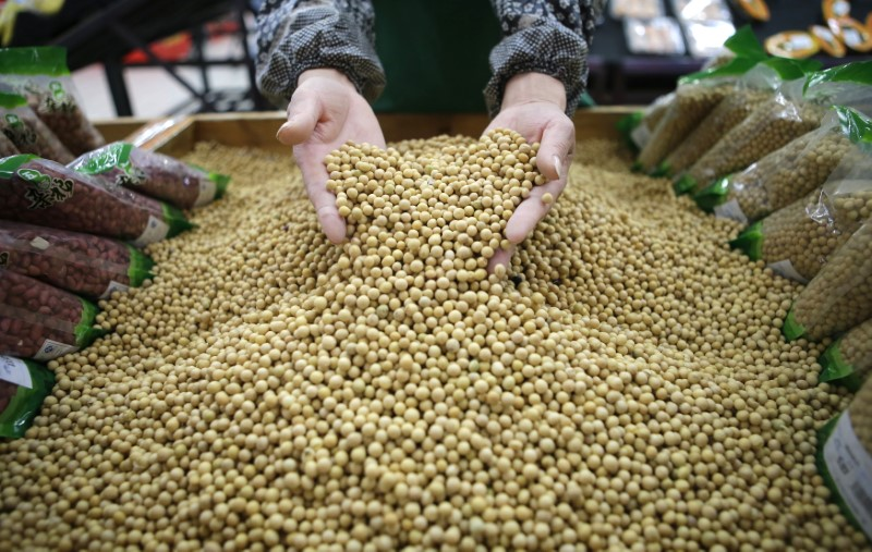An employee picks out bad beans from a pile of soybeans at a supermarket in Wuhan