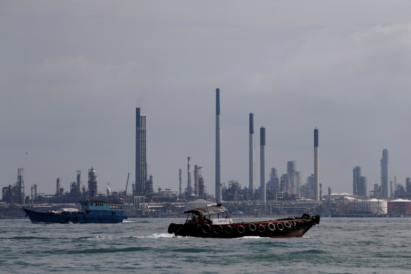 FILE PHOTO: Boats sail past Pulau Bukom oil refinery along the southern coast of Singapore