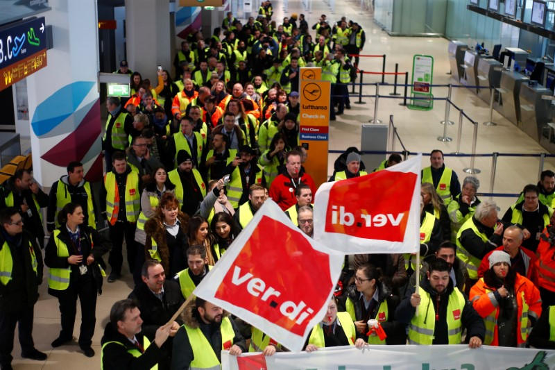 FILE PHOTO: Security personal of the Cologne-Bonn Airport wave flags of German union Verdi during a strike in Cologne