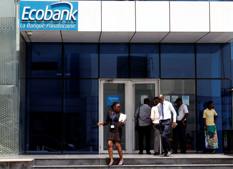 People walk at the entrance of Ecobank building in Abidjan