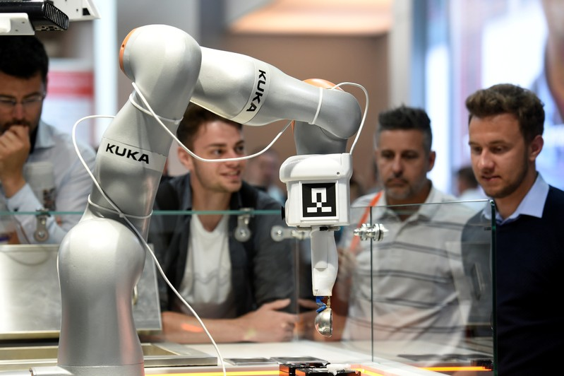 Visitors inspect a robot at the booth of KUKA at Hannover Messe, the trade fair in Hanover