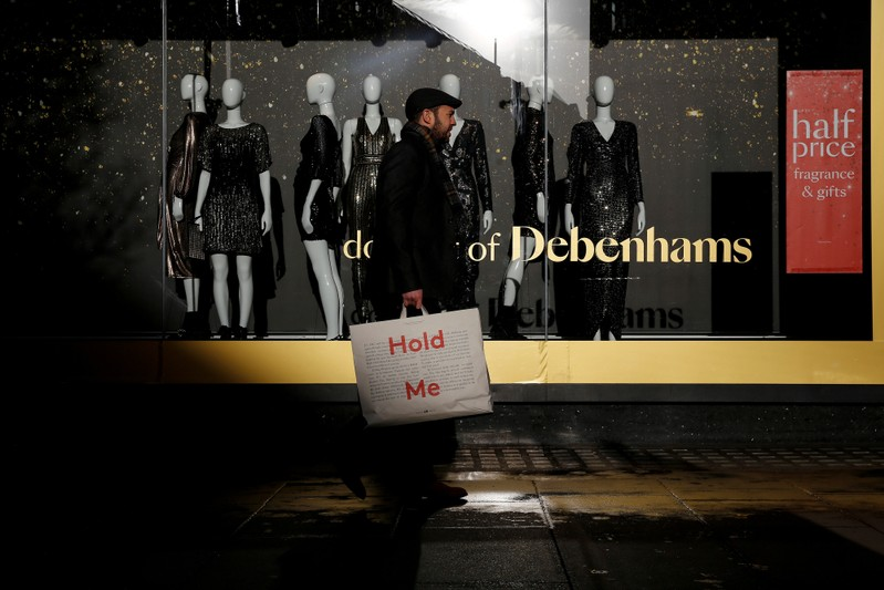 FILE PHOTO: Shoppers walk past a window display at the Debenhams department store on Oxford Street in London