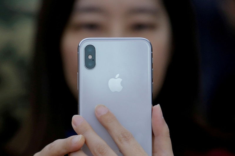 An attendee uses a new iPhone X during a presentation for the media in Beijing