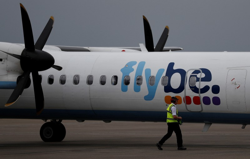 FILE PHOTO: An airport worker examines a flybe aircraft before it takes off from Liverpool John Lennon Airport in Liverpool northern England.