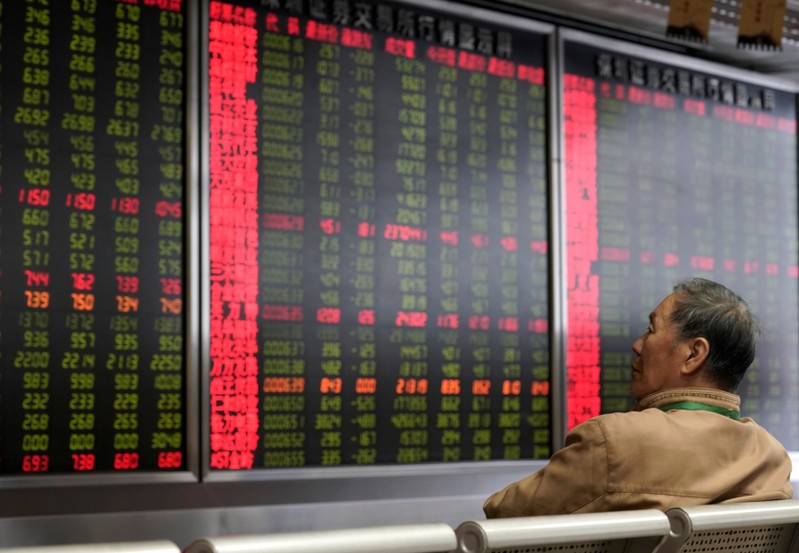 An investor watches a board showing stock information at a brokerage office in Beijing