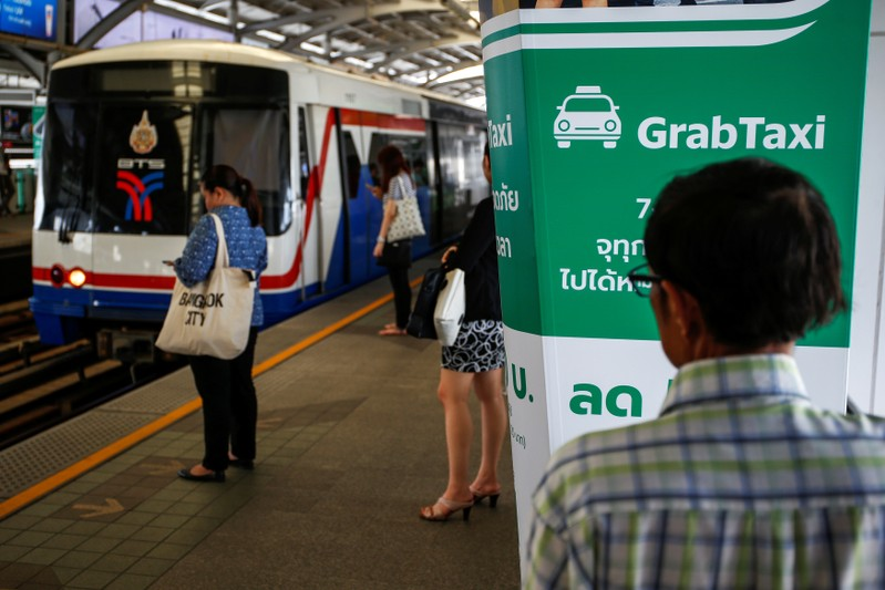 Passengers stand next to a GrabTaxi advertisement as they wait for skytrain at a station in Bangkok