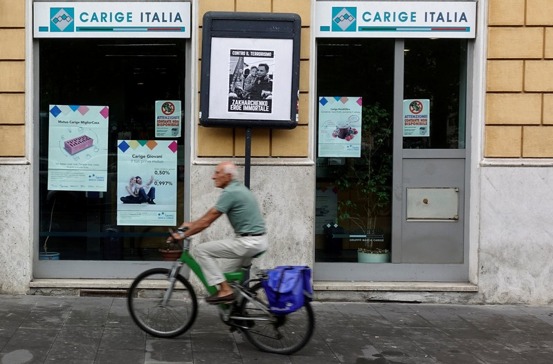 FILE PHOTO: A man rides a bicycle past a Carige bank in Rome