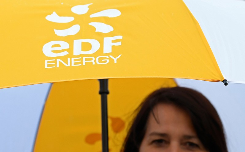 An employee carries an umbrella with the EDF energy logo near the Hinkley Point C nuclear power station near Cannington in southwest England