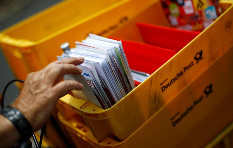 A postman of German mail services Deutsche Post AG delivers mail in Hanau