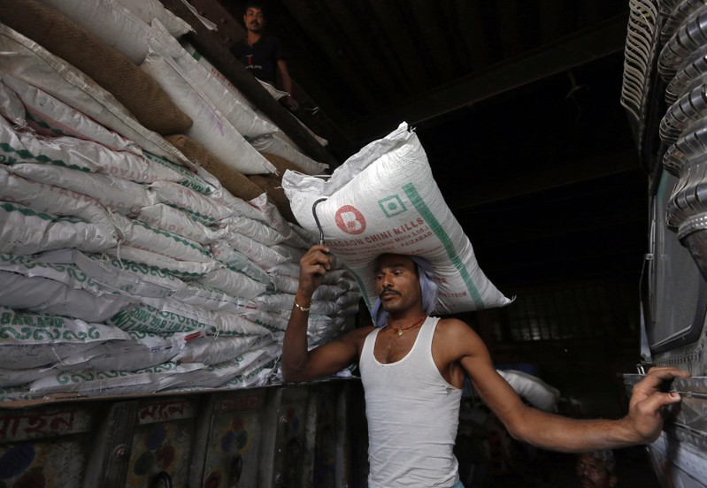 A labourer carries a sack of sugar to load it onto a supply truck at a market area in Kolkata
