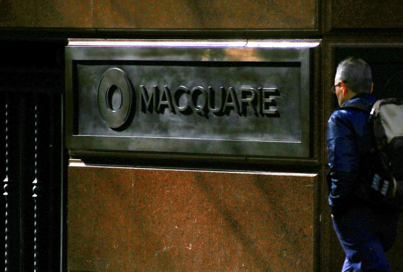 A pedestrian walks past the logo of Australia's biggest investment bank Macquarie Group Ltd which adorns a wall on the outside of their Sydney office headquarters in central Sydney, Australia