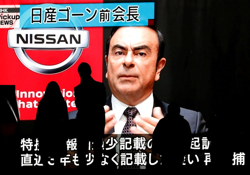 FILE PHOTO: Passersby are silhouetted as a huge street monitor broadcasts news reporting ousted Nissan Motor chairman Carlos Ghosn's indictment and re-arrest in Tokyo