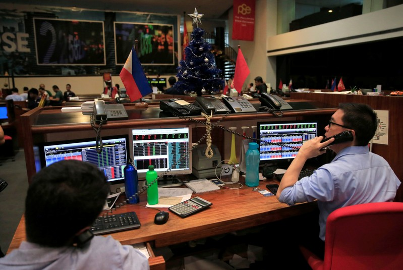 FILE PHOTO :Traders begin work on the first day of 2018 trading at the Philippine Stocks Exchange (PSE), as the benchmark index hits a new record high, in the financial district of Makati city, Metro Manila