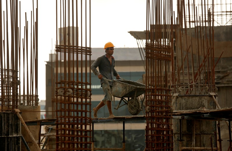 FILE PHOTO: A worker pushes a wheelbarrow to collect cement at a construction site of a residential building in Mumbai