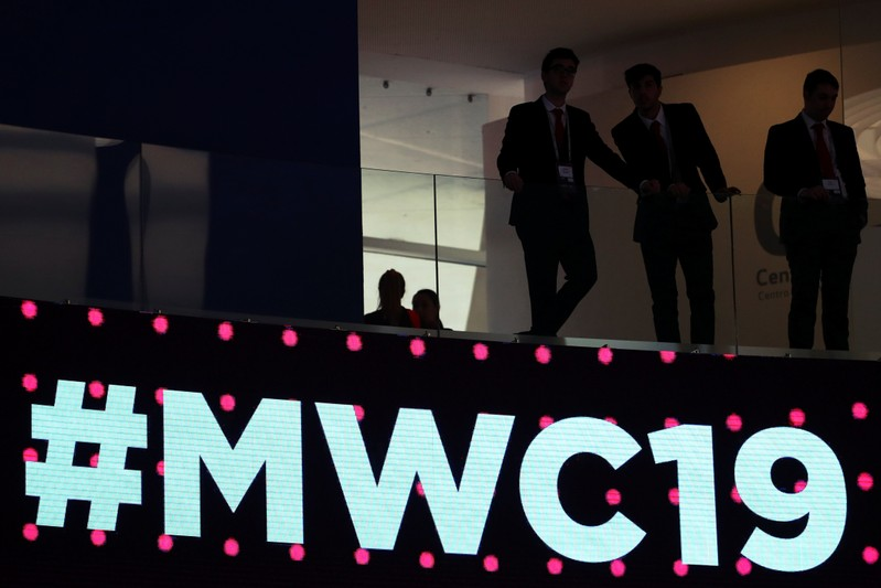 Men stand over a sign at the Mobile World Congress in Barcelona